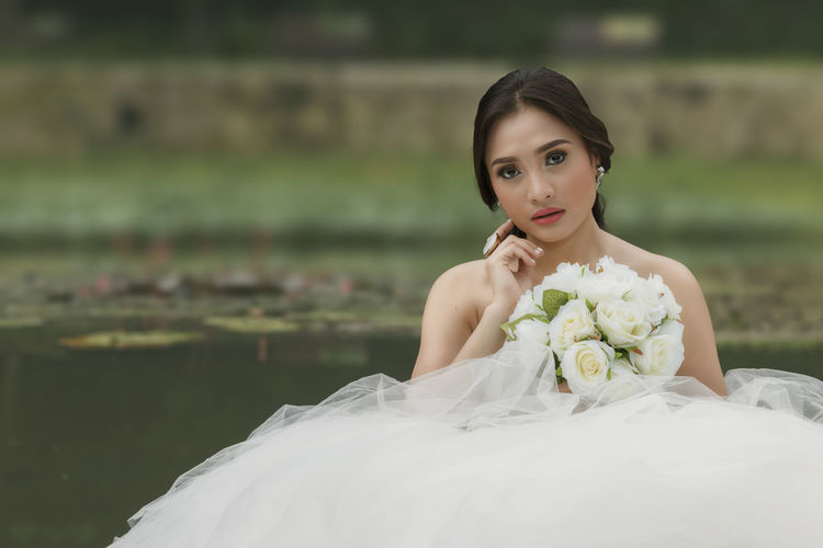Portrait Of Beautiful Bride Holding White Roses Bouquet Against Lake