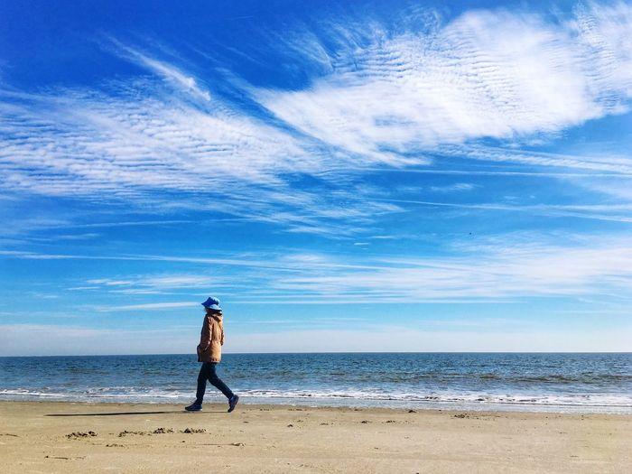 Full length of girl walking on beach against sky