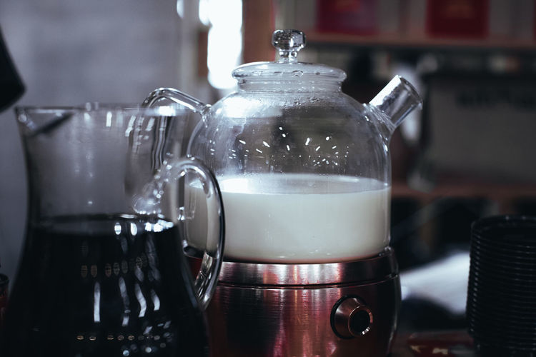 Glass teapot with white steamed milk for making indian masala tea. hot drink.