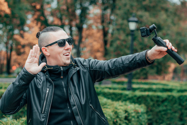 Young man wearing sunglasses filming with video camera in park
