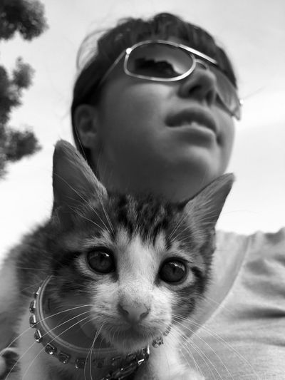 Close-Up Of Young Woman With Cat Standing Against Sky