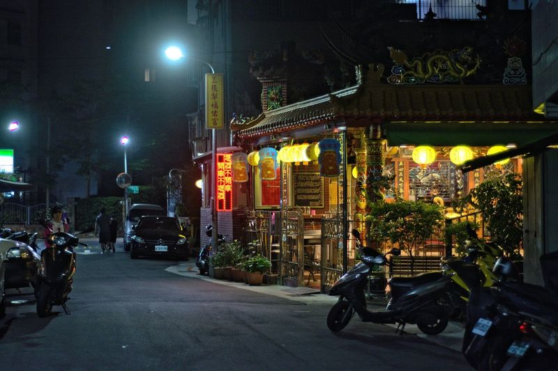 Street amidst illuminated buildings in city at night