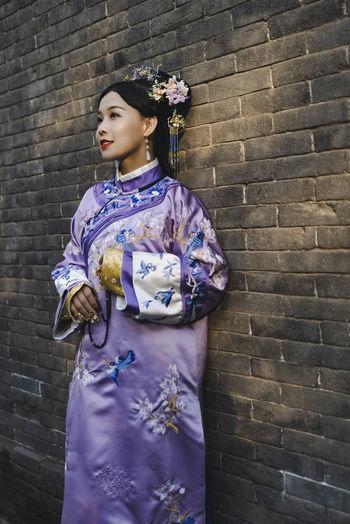 Woman wearing kimono standing against wall