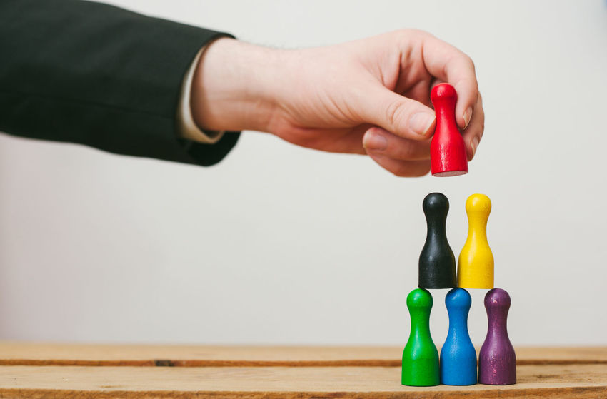 Business Team Building, diversity. Colorful pawns forming a pyramid, representing Trust Business Diversity Pyramid Teamwork Work Colorful Concept Conceptual Divers Hand Human Body Part Human Hand Ideas One Person Pawns Team Trust