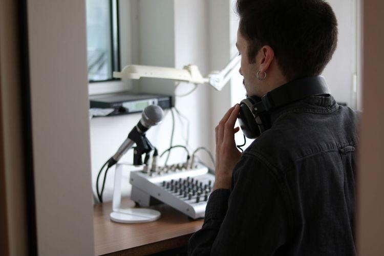 Rear view of man wearing headphones standing in recording studio