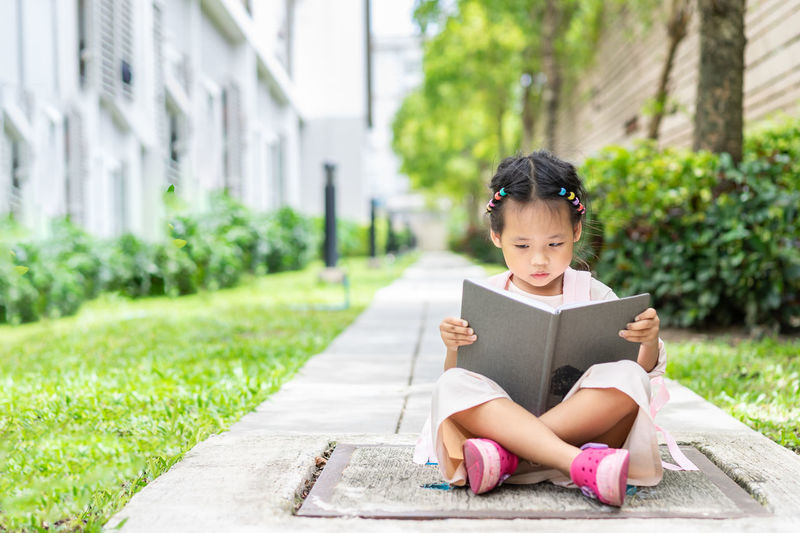 03da45a6874e little girl reading a book with backpack sitting in the park ready back to  school Females