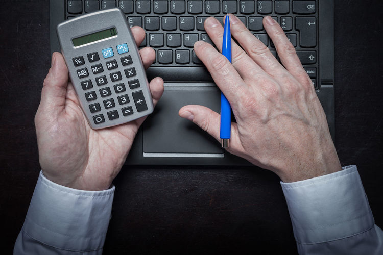 Cropped hands of businessman using calculator and laptop at desk