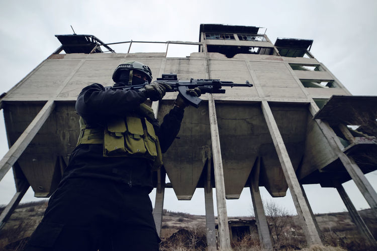 Low angle view of male soldier aiming gun while standing against built structure