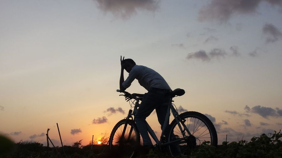 Man cycling against sky during sunset