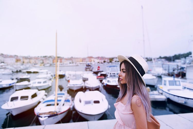 Woman standing at harbor against clear sky