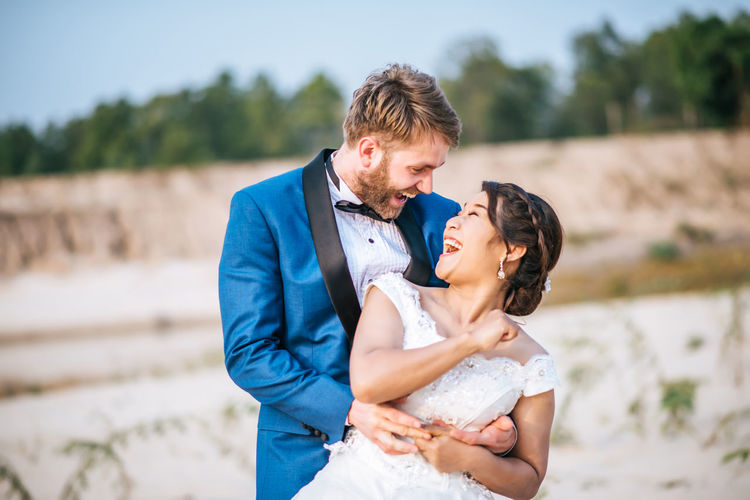 Happy couple embracing while standing outdoors