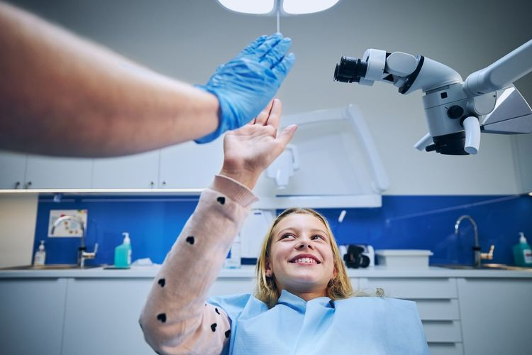 Smiling girl giving high-five to dentist