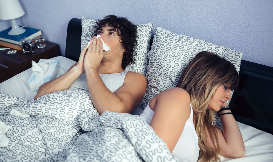 Sick man sneezing and covering nose with tissue lying on bed side to young woman sleeping. Sickness and healthcare concept. Bed Horizontal Lying Man Medicine Unhappy Woman Allergy Bedroom Cold Female Fever Flu Grippe Headache Illness Male Nasal Real People Sick Sickness Sneezing Temperature Two People Vertical
