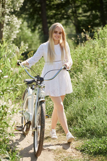 Portrait of smiling young woman with bicycle against plants
