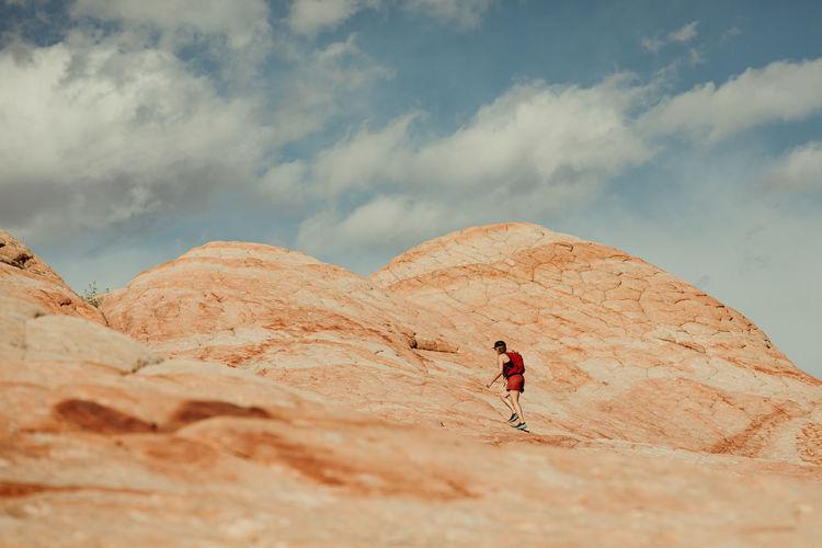 Full length of man climbing rock on land against sky