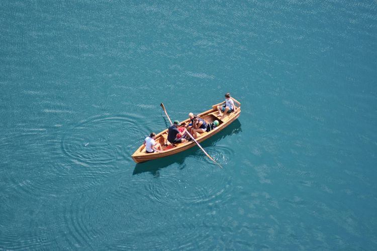 Aerial view of people sailing in boat at lake