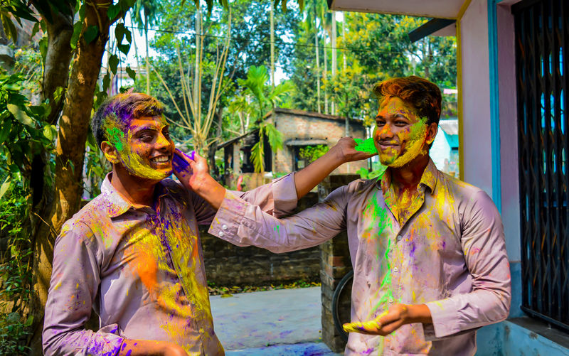 Male friends celebrating holi with colorful powder paint against trees