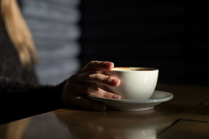 Woman holding cup of coffee in the dark room Copy Space Close-up Coffee - Drink Coffee Cup Day Drink Food And Drink Freshness Holding Human Body Part Human Hand Indoors  Lifestyles One Person People Real People Refreshment Table White Cup Women