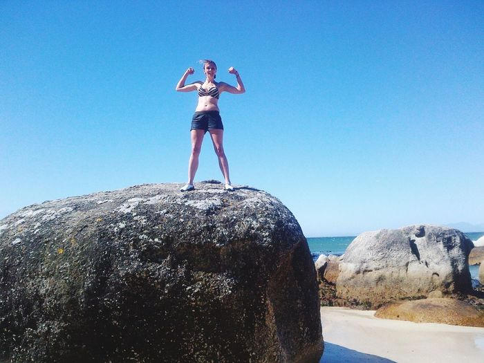 Low angle view of woman flexing muscles while standing on rock against sky