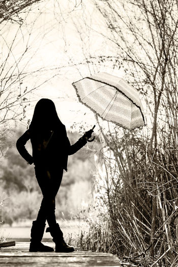 Full length of woman with umbrella standing by tree
