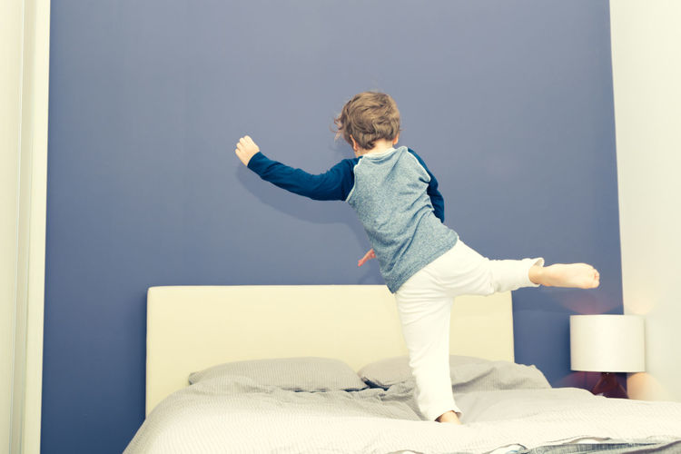 Boy playing on bed at home