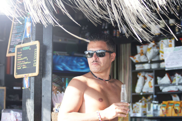 Portrait of shirtless man wearing sunglasses standing outdoors