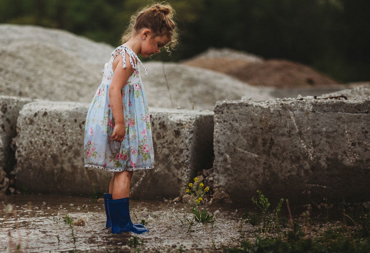 Girl standing in puddle looking at yellow flowers Rainboots Yellow Flower Child Childhood Curls Dress Flower Girls Innocence Lifestyles Nature One Person Puddle Springtime Standing