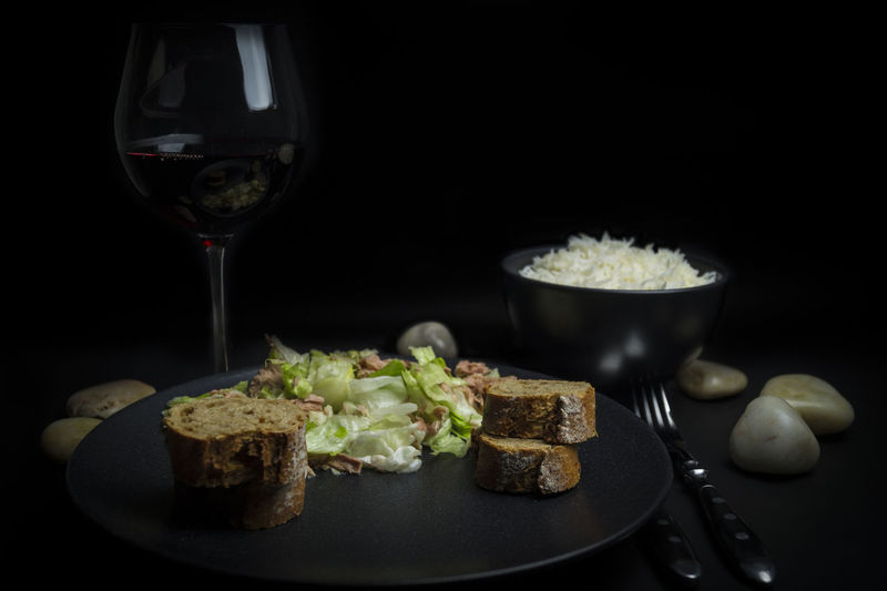 Close-up of fresh healthy meal served with wine against black background