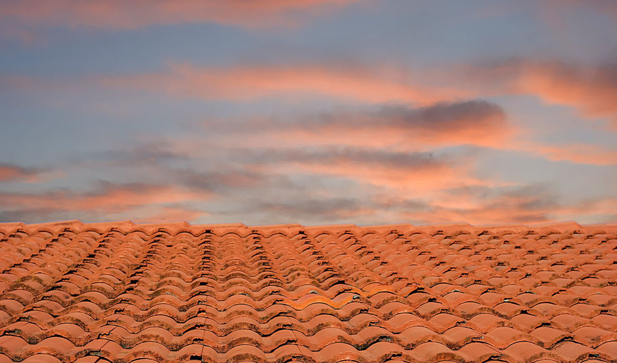 Roof of building against sky during sunset