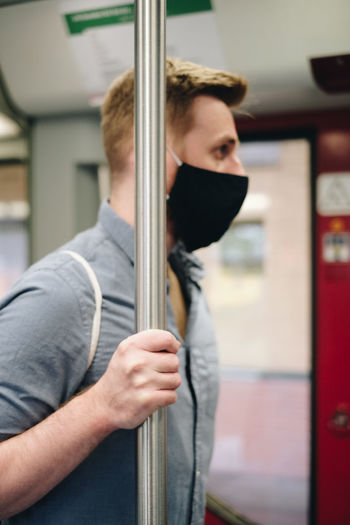 Side view of man wearing mask standing in subway train