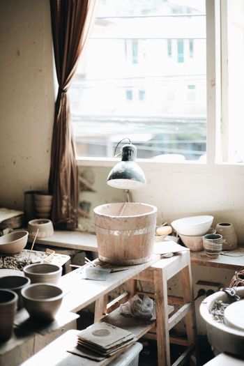 Bowls and lamp on table in workshop