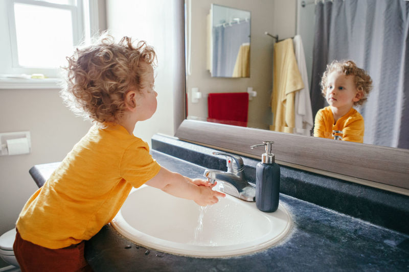Little caucasian boy toddler washing hands in bathroom at home. health hygiene and morning routine