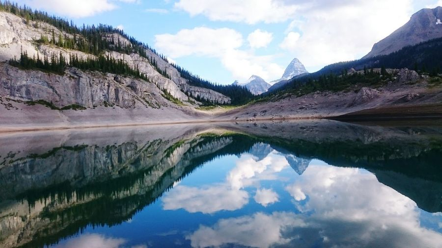 Scenic View Of Mountains Reflecting In Calm Lake Against Sky