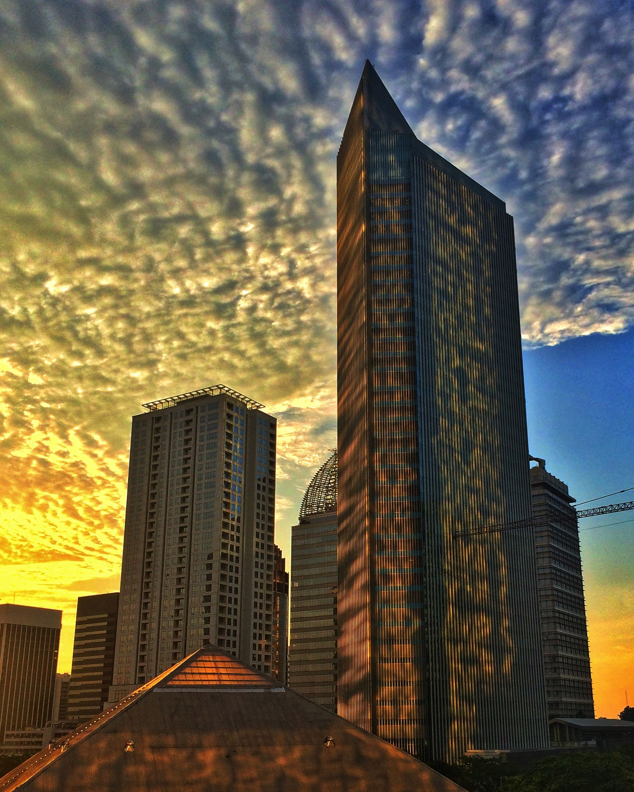 architecture, building exterior, built structure, skyscraper, modern, sky, office building, city, tall - high, low angle view, cloud - sky, tower, cloudy, cloud, building, sunset, tall, outdoors, no people, city life