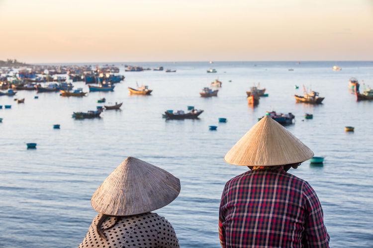 Unidentified vietnamese women overlooking fishermans bay full of fishing boats.
