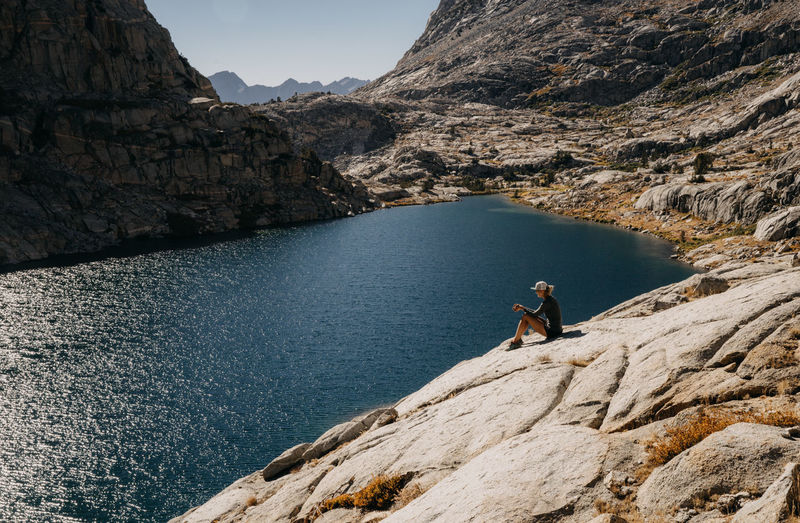 John Muir Trail Sierra Nevada Mountains Pacific Crest Trail Lake Mountain Lake Mountain Lake View California One Person Hiking Hiker Girl Hiker Woman Hiker Thru Hiking Rock Rock - Object Leisure Activity Solid Mountain Real People Lifestyles Water Beauty In Nature Rock Formation Nature People Day Scenics - Nature Adventure Tranquility Non-urban Scene Mountain Range Formation Outdoors