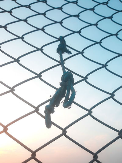 Low angle view of rope tied on chainlink fence against sky