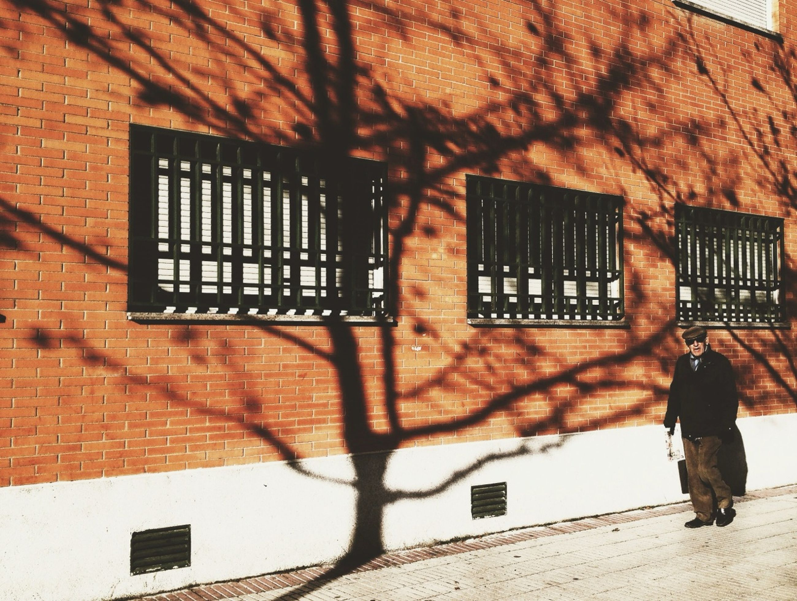 architecture, building exterior, built structure, brick wall, wall - building feature, lifestyles, window, leisure activity, men, house, shadow, building, outdoors, person, wall, sunlight, day, full length