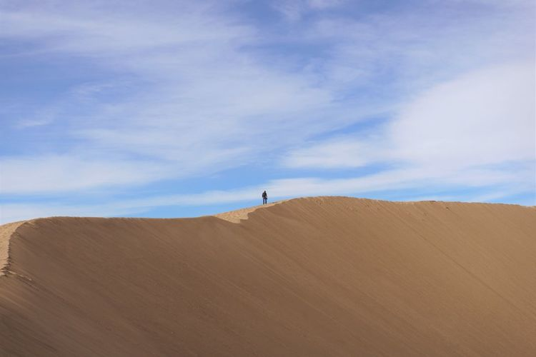 Person standing on desert against sky