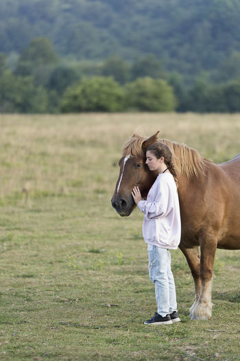 Teenage girl with horses on field