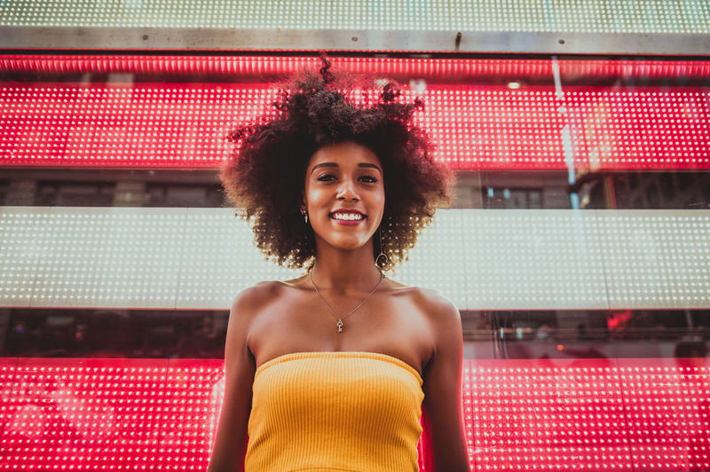 Low Angle Portrait Of Happy Young Woman Standing Against Neon American Flag In City