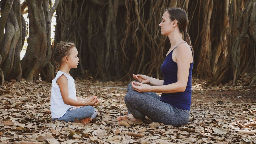 Side view of mother and daughter meditating while sitting on land