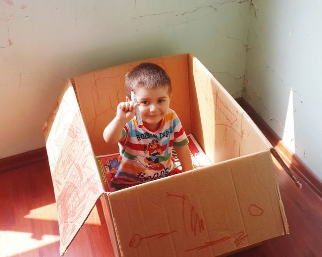 Portrait of happy boy sitting in box at home