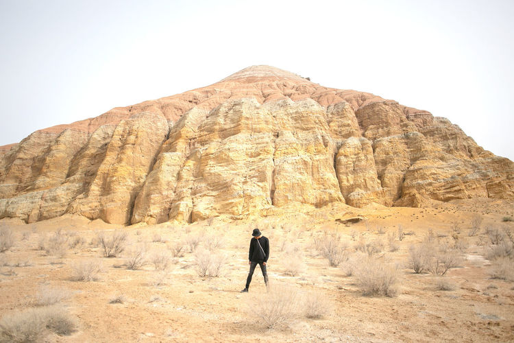 One Person Rock Rock - Object Lifestyles Rock Formation Leisure Activity Scenics - Nature Solid Real People Beauty In Nature Nature Mountain Rear View Sky Physical Geography Non-urban Scene Day Men Geology Travel Climate Mountain Range Formation Arid Climate Outdoors Eroded