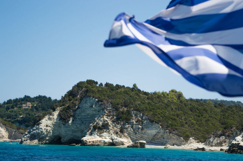 Greek Flag Waving Against Rocky Mountain By Sea
