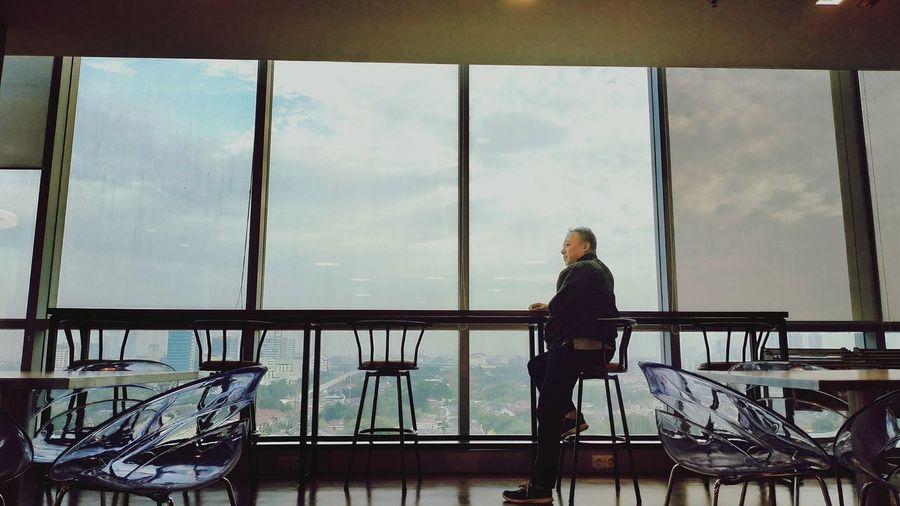 Man sitting on chair against sky seen through glass window