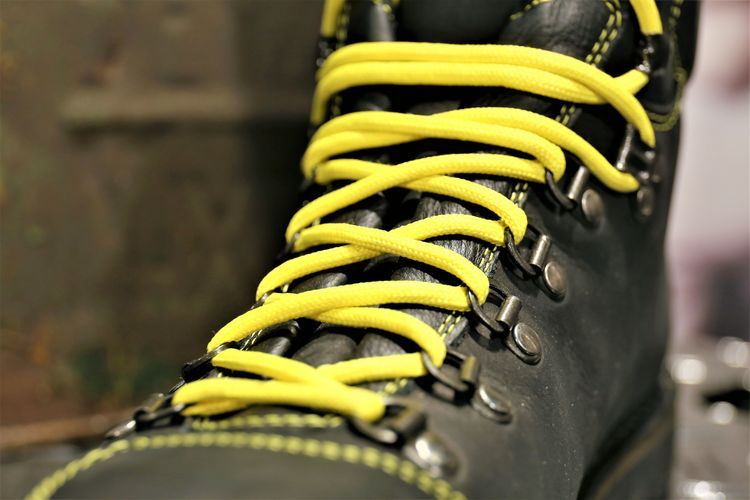 Close-up of boot with yellow shoelace