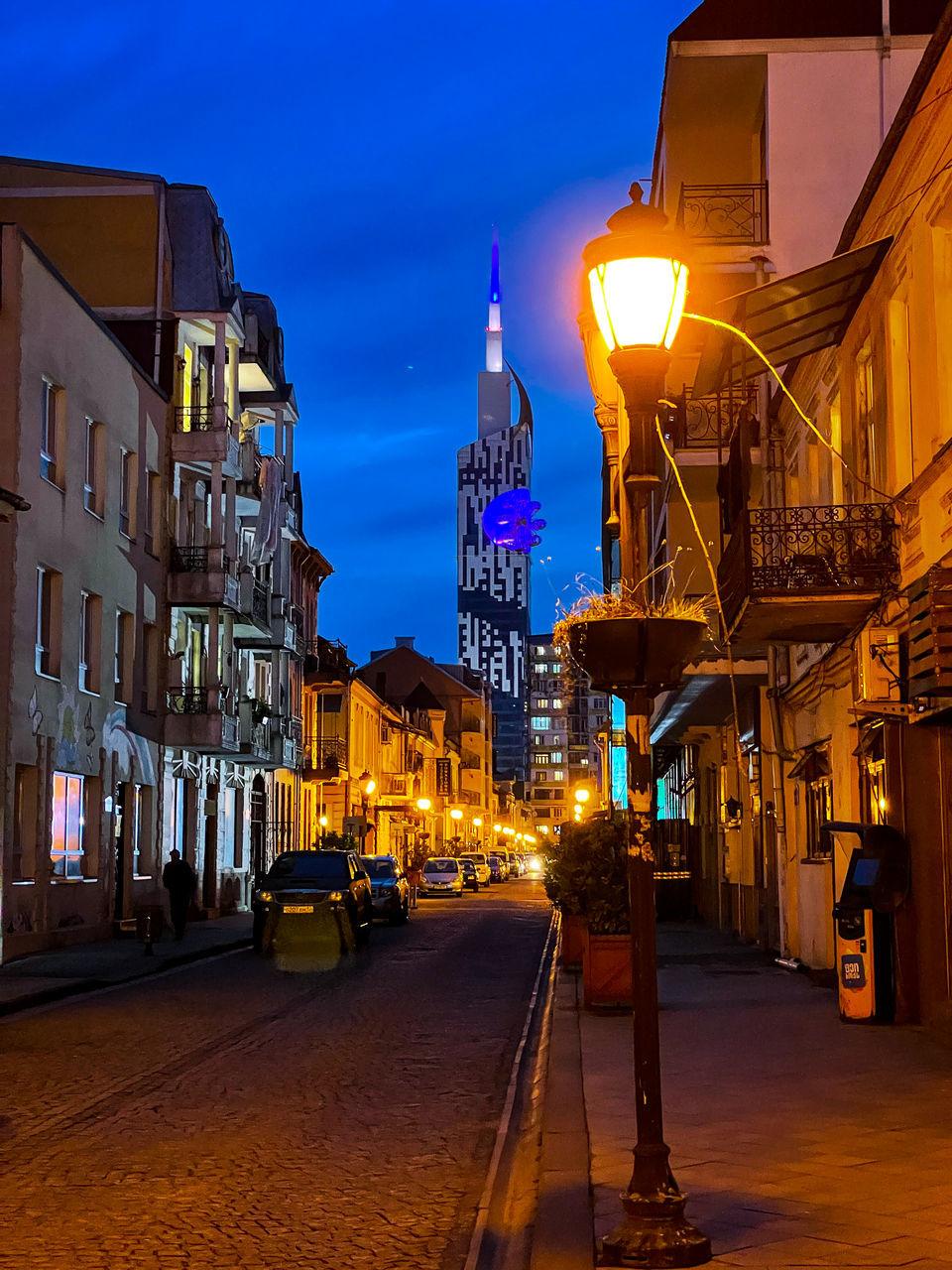 ILLUMINATED CITY STREET BY BUILDINGS AT NIGHT