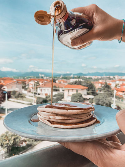 Midsection of person holding pancake against sky