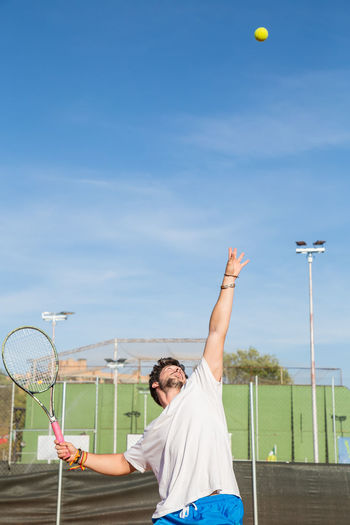 Professional tennis player throwing ball in the air before hitting it. Adult Athlete Athletic Court Kick Lifestyle Sunlight Tennis Active Air Ball Competition Enjoy Healthy Hit Match One Person Player Professional Racket Serve Sky Sport Sports Clothing Throw
